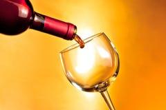 瓶填装在金黄背景的红葡萄酒起点一块玻璃 免版税库存照片
