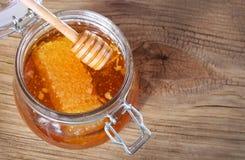 瓶子与蜂窝的在木背景的蜂蜜和浸染工 免版税库存照片