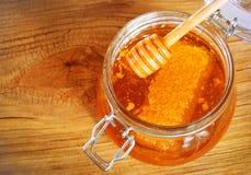 瓶子与蜂窝的在木背景的蜂蜜和浸染工 免版税库存图片