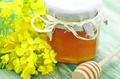 瓶子在一个瓶子的可口蜂蜜用油菜籽开花 免版税库存图片