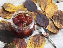 瓶子在桌上的果酱与叶子 免版税图库摄影