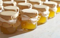 瓶子在白色桌果酱的蜂蜜 库存照片