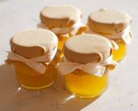瓶子在白色桌果酱的蜂蜜 库存图片