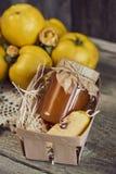 瓶子在篮子的与叶子的果酱和柑橘在木土气ba 免版税库存图片
