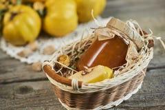 瓶子在篮子的与叶子的果酱和柑橘在木土气ba 免版税库存照片