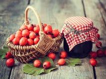 瓶子在篮子的果酱和山楂树莓果在桌上 免版税图库摄影