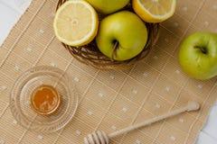 瓶子在纺织品桌布的蜂蜜和一碗果子 图库摄影