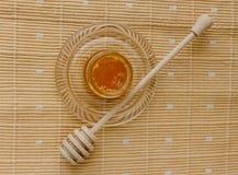 瓶子在纺织品桌布的蜂蜜 免版税库存图片