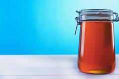 瓶子在蓝色背景的蜂蜜 免版税库存照片