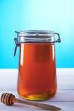 瓶子在蓝色背景的蜂蜜 免版税库存图片