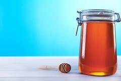 瓶子在蓝色背景的蜂蜜 图库摄影