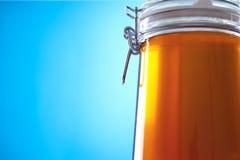 瓶子在蓝色背景的蜂蜜 免版税图库摄影
