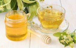 瓶子新鲜的甜菩提树蜂蜜,茶在木桌和菩提树花的 免版税库存照片