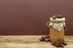 瓶子果酱八角和肉桂条对布朗和木背景 免版税图库摄影