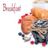瓶子果酱,新鲜的莓果,新月形面包和咖啡,被隔绝 免版税库存图片