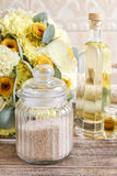 瓶子海盐和瓶在木桌上的精油 免版税库存图片