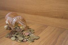 瓶子玻璃充分在木桌上的欧洲硬币 免版税库存图片