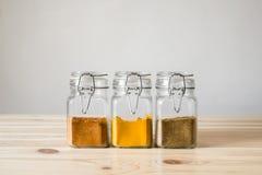 瓶子用在轻的木桌上的香料 图库摄影