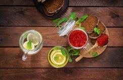瓶子用红色鱼子酱和面包 库存照片