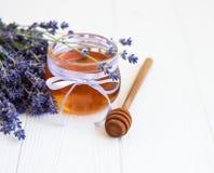 瓶子用蜂蜜和新鲜的淡紫色花 库存图片