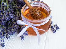 瓶子用蜂蜜和新鲜的淡紫色花 免版税库存照片