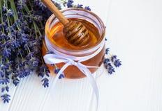 瓶子用蜂蜜和新鲜的淡紫色花 图库摄影