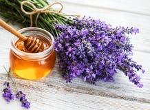 瓶子用蜂蜜和新鲜的淡紫色 免版税库存图片