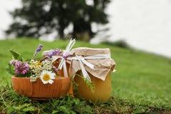瓶子用蜂蜜和花在碗 免版税库存照片