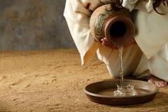 从瓶子的耶稣倾吐的水 库存照片