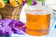 瓶子糖酱或蜡蜂蜜的构成去除与紫色手套和花的头发的-去壳和秀丽概念 免版税图库摄影