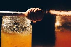 瓶子蜂蜜用在木桌关闭的百吉卷与蜂蜜浸染工 免版税库存图片