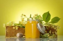 瓶子蜂蜜,与蜂蜂窝的木制框架在黄色背景 免版税库存图片