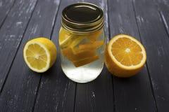 瓶子鲜美新鲜的柠檬水用柠檬在背景中 免版税库存图片