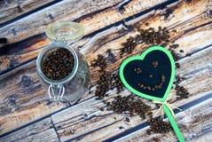 瓶子黑板的coffe豆、微笑和心脏 库存照片