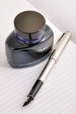 瓶干净的喷泉墨水位于的笔页 库存照片