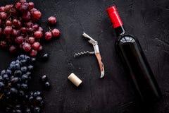 瓶开放酒 葡萄和拔塞螺旋在黑背景顶视图 免版税库存图片
