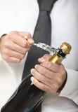 瓶开放香槟的人 免版税库存图片