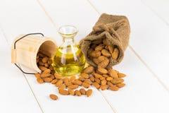 瓶扁桃仁油和杏仁在白色木背景 免版税库存照片