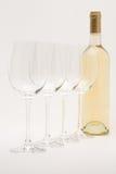 瓶排队的白葡萄酒葡萄酒杯 库存图片