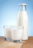 瓶新鲜的牛奶和二块玻璃是木桌 库存照片