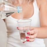 瓶杯子塑料倾吐的水 库存图片