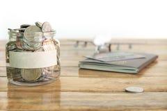 瓶概念美元货币储蓄 收在金钱瓶子的金钱您的概念的 有硬币、飞机玩具和护照的金钱瓶子 图库摄影