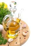 瓶橄榄油、大蒜、香料和新鲜的草本在船上 免版税库存图片