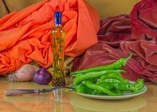 瓶橄榄油、葱和青椒在橙色backg 免版税库存照片