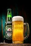 瓶海涅肯与玻璃的储藏啤酒在木桌上 免版税库存图片