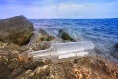 瓶消息礁石 库存照片