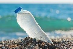 瓶淡水在沙子 免版税库存照片