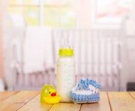 瓶牛奶、蓝色赃物和橡胶鸭子在白色 免版税图库摄影