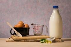 瓶牛奶、鸡蛋、量杯和匙子 免版税库存照片