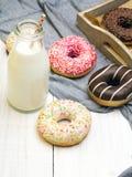 瓶牛奶和五颜六色的油炸圈饼用巧克力和结冰, 免版税库存图片